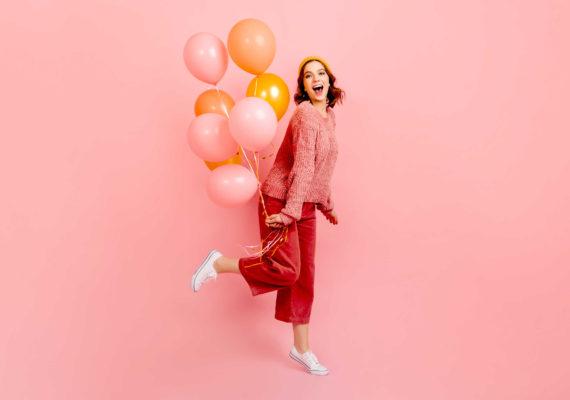 кокетливая девушка празднует день рождения с воздушными шарами стоит на одной ноге подняв втору