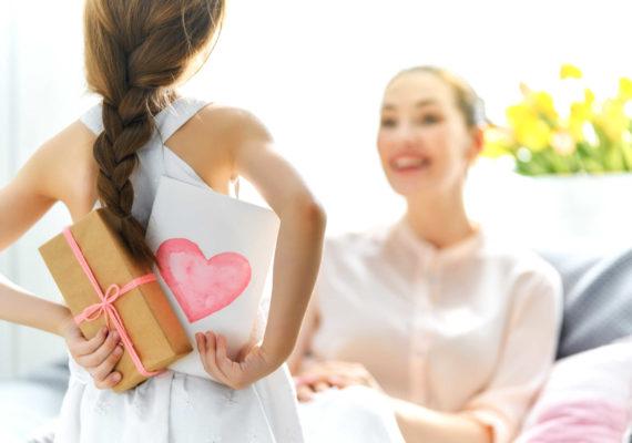 девочка прячет от мамы поздравительную открытку с сердечком на день рождения
