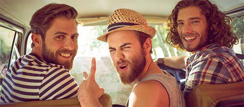 Трое молодых бородатых парней на летнем отдыхе в машине оборачиваются назад улыбаясь и показывая знаки руками