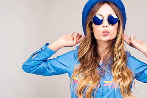 Красивая стильная девушка в голубой рубашке, шляпе и синих солнечных очках со светлыми вьющимися волосами
