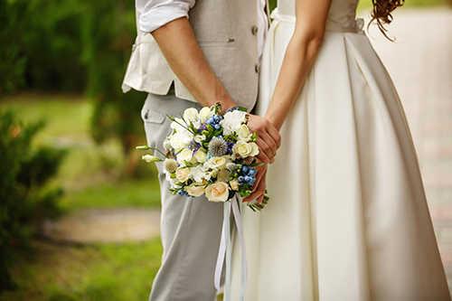 Нижняя часть молодожёнов в белом со свадебным букетом в руках на фоне парка