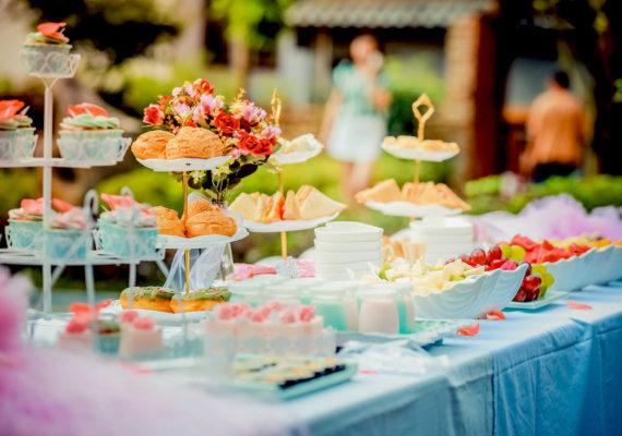 накрытый сладкий стол с пирожными, фруктами, сладостями и тортами для банкета с аппетитным угощением на свежем воздухе для дня рождения и юбилея