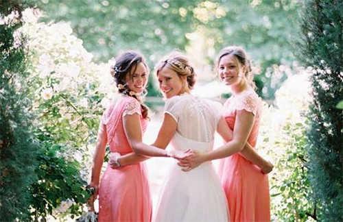 Невеста в белом и две подружки невесты в розовых платьях оборачиваются к фотографу позируя на тропинке в парке