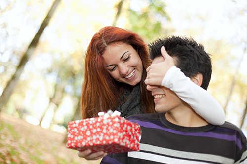 Девушка обнимает сзади парня закрывая ему глаза и протягивая вперед красную коробку с подарком на фоне деревьев