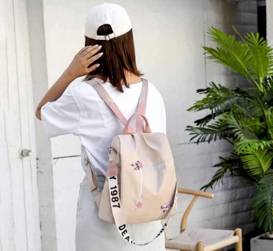девушка в белом с светлым рюкзаком стоит спиной
