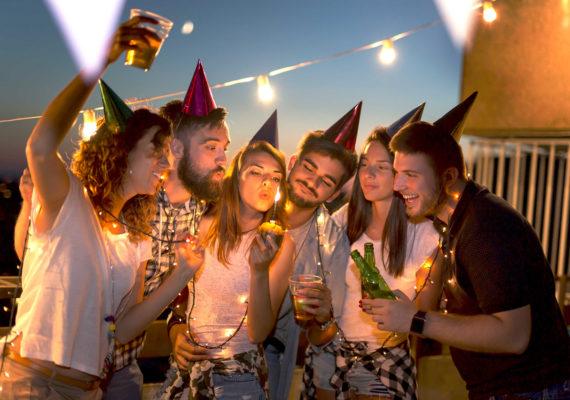 веселая кампания поздравляет девушку с днем рождения в вечернем кафе со светодиодными огоньками и свечкой которую именинница задувает