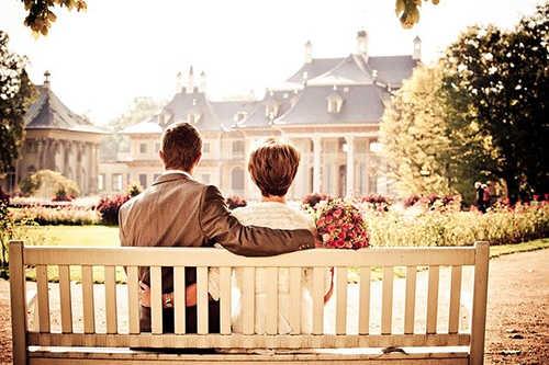 мужчина и женщина со спины сидят на белой лавочке и смотрят на городской вид из парка