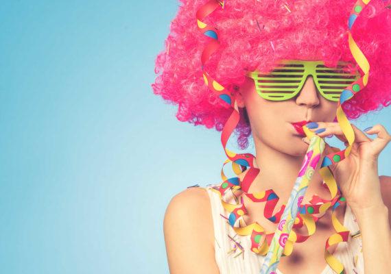 девушка в смешном розовом парике и огромных желтых очках празднует день рождения