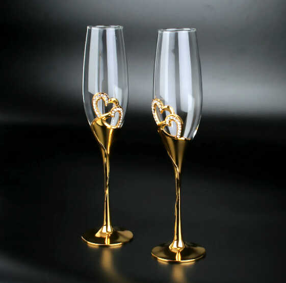 два золотых бокала со стразами для шампанского на черном фоне