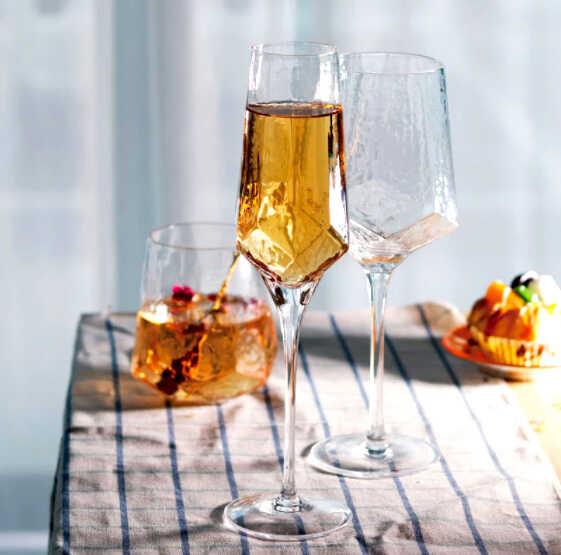 граненные бокалы и стаканы для вина и сока на домотканой скатерти рядом с пирожным на блюдце