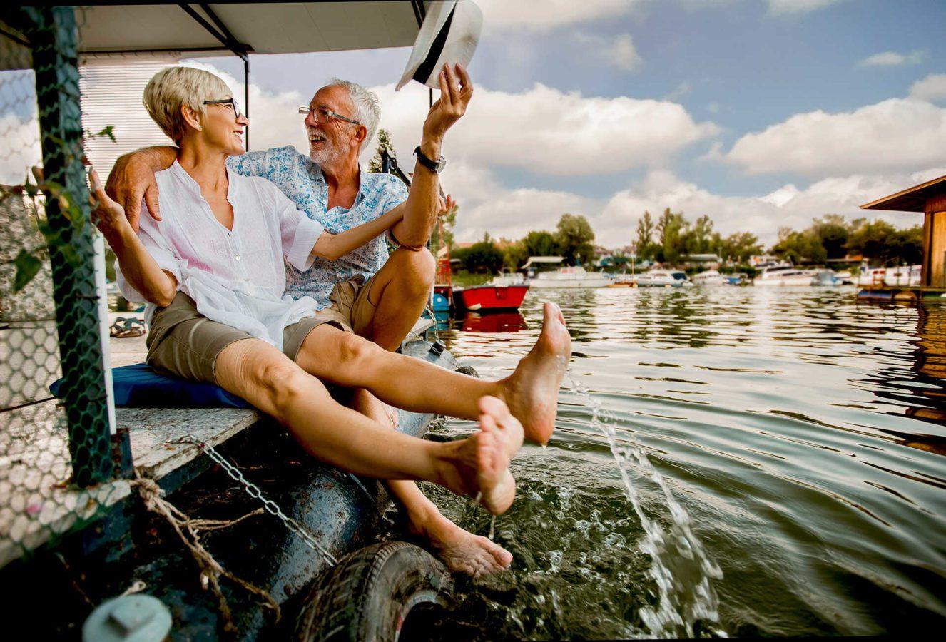 пожилые мужчина и женщина обнимаются и смеются на яхте на воде