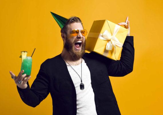 мужчина с бородой знает что подарить мужчине и держит в руках коробку с подарком и зеленый коктейль с трубочкой на желтом фоне