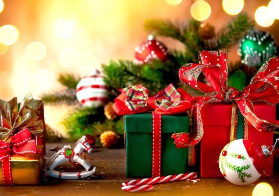 новогодние и рождественские подарки на фоне елки и елочных игрушек