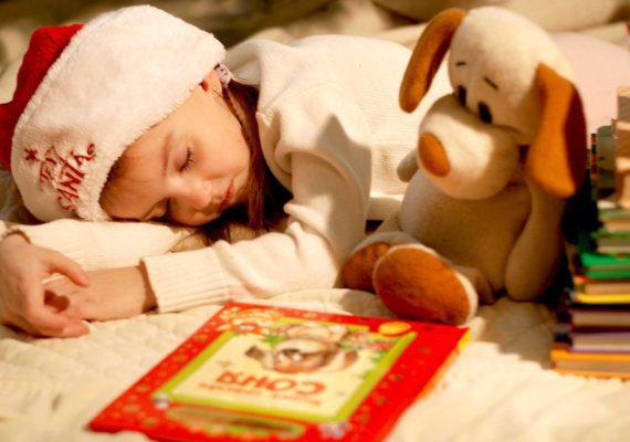 спящая девочка в колпачке санта клауса с книжками и игрушечной собачкой