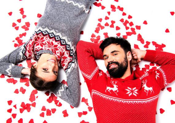 парень и девушка в зимних свитерах лежат в окружении красных сердечек на белом фоне