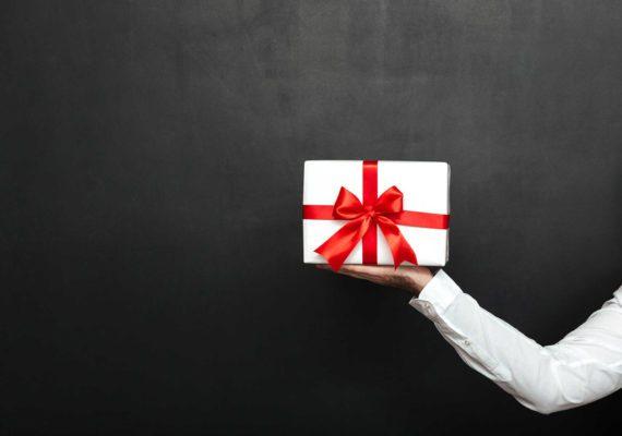 белый подарок с красным бантом в руке на черном фоне