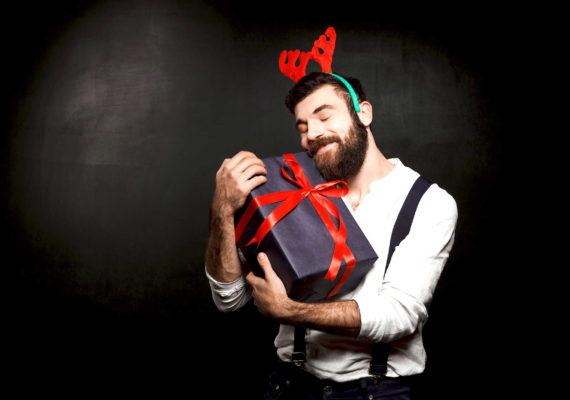 мужчина в белом с черной коробкой подарков с красной лентой на черном фоне