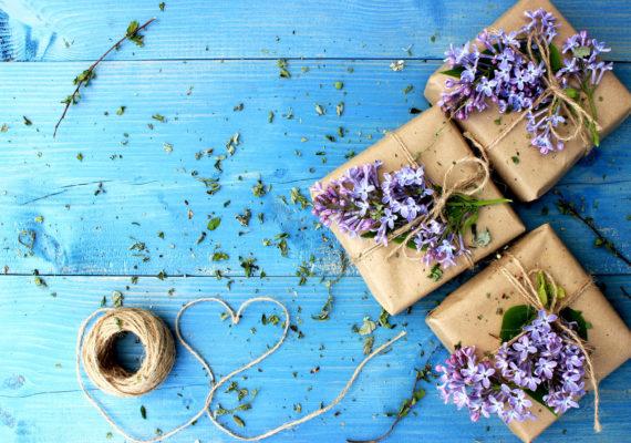 подарки девушке без повода и на праздники в крафтовой упаковке с маленькими сиреневыми цветами на голубом дощатом столе с мотком веревочки