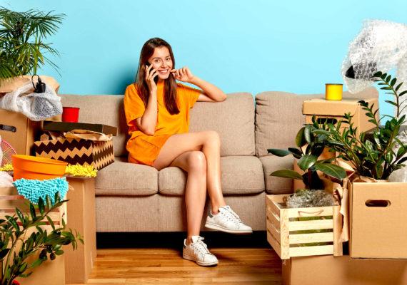 веселая девушка в желтом платье сидя на диване в комнате с упакованными в коробки и ящики вещами комнатными цветами и мебелью разговаривает по телефону